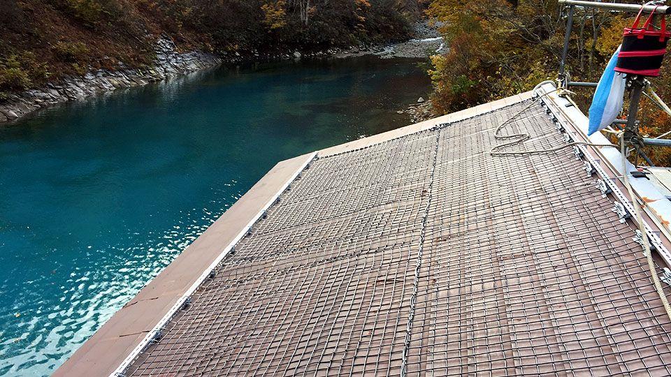 融雪ネットをカッサ川調整池除塵機建屋屋根に施工